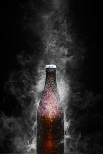 黒いバック背景のビール瓶と煙の写真素材 [FYI04777073]