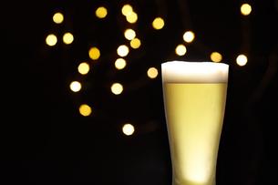 ビールグラスに入ったビールとキラキラライトの写真素材 [FYI04777075]