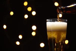 キラキラした空間でビールをグラスに注いでいるところの写真素材 [FYI04777076]