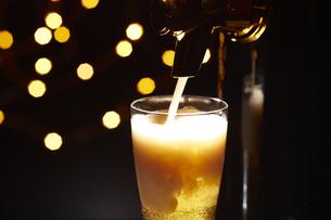 キラキラした空間でビールをグラスに注いでいるところの写真素材 [FYI04777078]