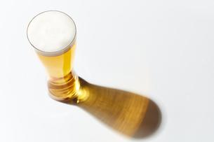白い天板の上にあるビールが入ったグラスの写真素材 [FYI04777081]