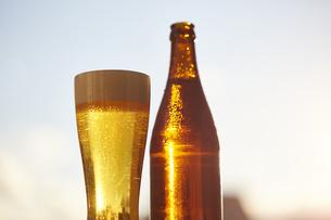 外に置かれたビアグラスとビール瓶の写真素材 [FYI04777087]