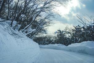 山の雪の踏み固めた道路を車で走る光景の写真素材 [FYI04777923]