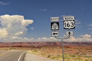 道路標識と赤い岩へ続く道の写真素材 [FYI04777931]