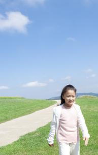 芝生を歩く女の子の写真素材 [FYI04778088]