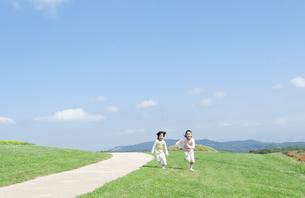 芝生を走る女の子と男の子の写真素材 [FYI04778089]