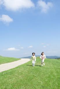 芝生を走る女の子と男の子の写真素材 [FYI04778090]