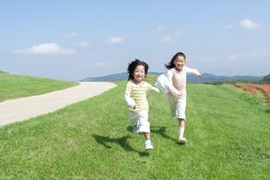 芝生を走る女の子と男の子の写真素材 [FYI04778091]