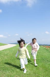 芝生を走る女の子と男の子の写真素材 [FYI04778092]