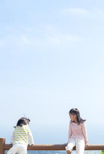 柵に座る女の子と男の子の写真素材 [FYI04778095]