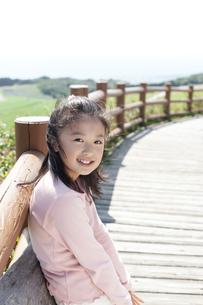 柵にもたれる女の子の写真素材 [FYI04778098]