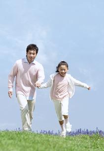 手をつないで走る親子の写真素材 [FYI04778108]