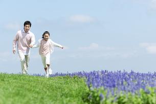 手をつないで走る親子の写真素材 [FYI04778109]