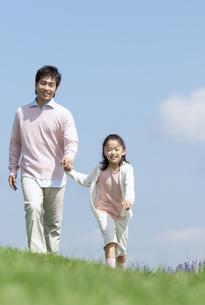 手をつないで走る親子の写真素材 [FYI04778112]