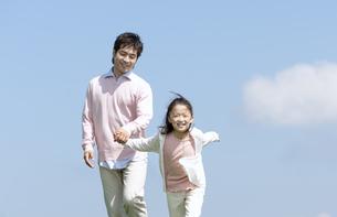 手をつないで走る親子の写真素材 [FYI04778113]
