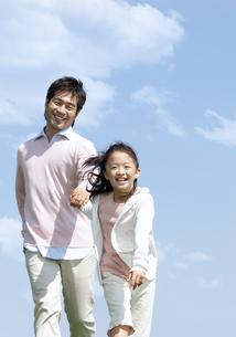 手をつないで走る親子の写真素材 [FYI04778117]