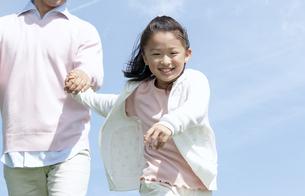 手をつないで走る親子の写真素材 [FYI04778118]