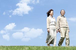 芝生を歩くシニア女性の写真素材 [FYI04778241]