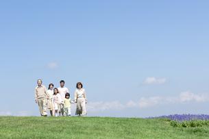 芝生を歩く三世代家族の写真素材 [FYI04778252]