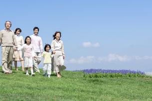 芝生を歩く三世代家族の写真素材 [FYI04778254]