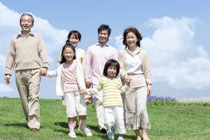 芝生を歩く三世代家族の写真素材 [FYI04778256]
