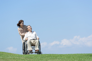 車椅子で散歩するシニア夫婦の写真素材 [FYI04778276]