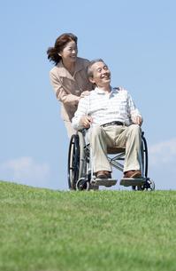 車椅子で散歩するシニア夫婦の写真素材 [FYI04778277]