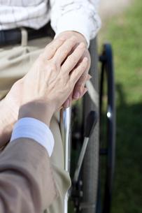 車椅子に乗る男性の手を握る女性の写真素材 [FYI04778301]