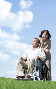 車椅子で散歩するシニア夫婦の写真素材 [FYI04778307]