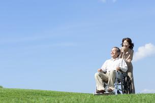 車椅子で散歩するシニア夫婦の写真素材 [FYI04778308]