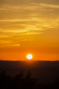 オレンジ色の空とシルエットになった大地と沈む太陽の風景の写真素材 [FYI04778935]