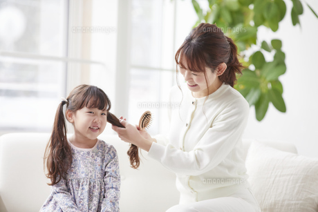ソファに座りヘアブラシを持ち髪の手入れをする母親と娘の写真素材 [FYI04779189]