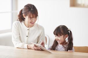 タブレット端末を操作する子供と母親の写真素材 [FYI04779190]