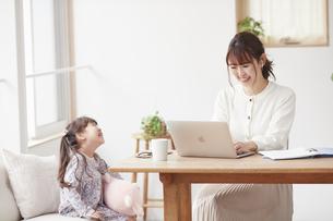 自宅で仕事をする母親と遊ぶ娘の写真素材 [FYI04779191]