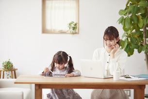 自宅で仕事をする母親と遊ぶ娘の写真素材 [FYI04779192]