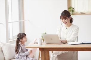 自宅で仕事をする母親と遊ぶ娘の写真素材 [FYI04779194]