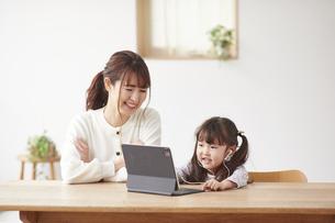 タブレットPCでオンライン通話をする子供と母親の写真素材 [FYI04779195]