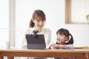 タブレットPCでオンライン通話をする子供と母親の写真素材 [FYI04779201]