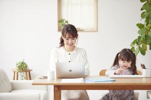 自宅で仕事をする母親と遊ぶ娘の写真素材 [FYI04779202]