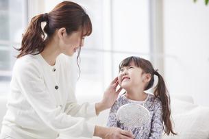 ソファに座り鏡を持つ娘と母親の写真素材 [FYI04779207]