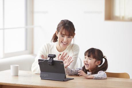 タブレットPCでオンライン通話をする子供と母親の写真素材 [FYI04779208]