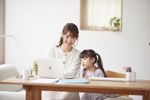 自宅で仕事をする母親と遊ぶ娘の写真素材 [FYI04779209]