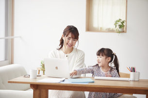 自宅で仕事をする母親と遊ぶ娘の写真素材 [FYI04779212]