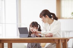 タブレット端末を操作する子供と母親の写真素材 [FYI04779213]