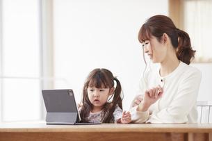 タブレット端末を操作する子供と母親の写真素材 [FYI04779216]