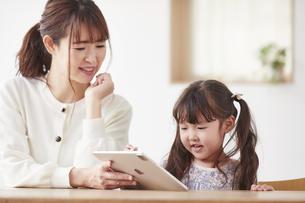 タブレット端末を操作する子供と母親の写真素材 [FYI04779226]