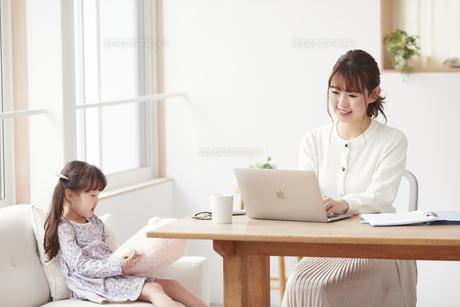 自宅で仕事をする母親と遊ぶ娘の写真素材 [FYI04779228]