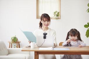 オンライン会議をしながら自宅で仕事をする母親と遊ぶ娘の写真素材 [FYI04779264]