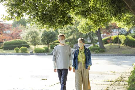 マスクをつけて公園を散歩する日本人シニア夫婦の写真素材 [FYI04779354]