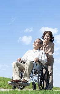 車椅子で散歩するシニア夫婦の写真素材 [FYI04779436]